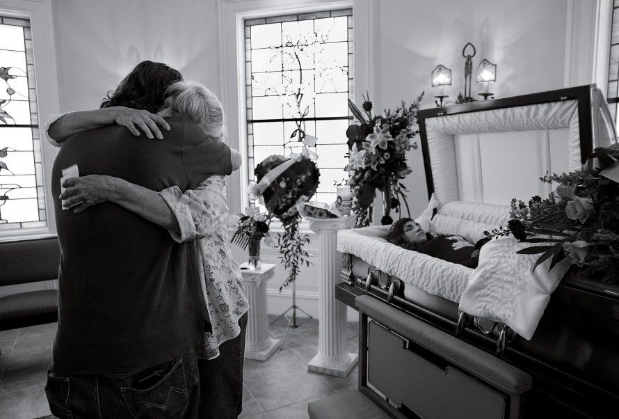 Fotó: <b>James Nachtwey</b>: A 67 éves Cheryl Schmidtchent az unokájának temetésén vigasztalják Manhattanben, 2017. szeptember 17-én. A 24 éves Michaela Gingras heroinfüggő volt.