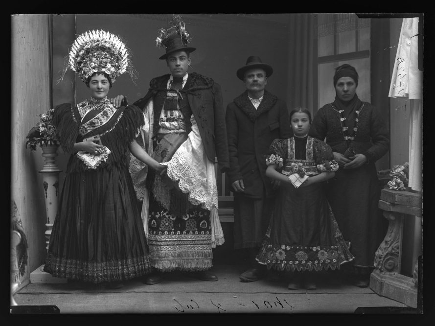 Fotó: Kis András és családja hagyományos matyó öltözetben. A menyasszony fején jellegzetes, színes selyemvirágokból kötött menyasszonyi koszorú. A férj fehér lyukhímzéses lobogós ujjú ingben, díszesen hímzett surcban (kötény)<br> Mezőkövesd, 1910-es évek Weissbach Rilly és testvére felvétele Néprajzi Múzeum, F 27626