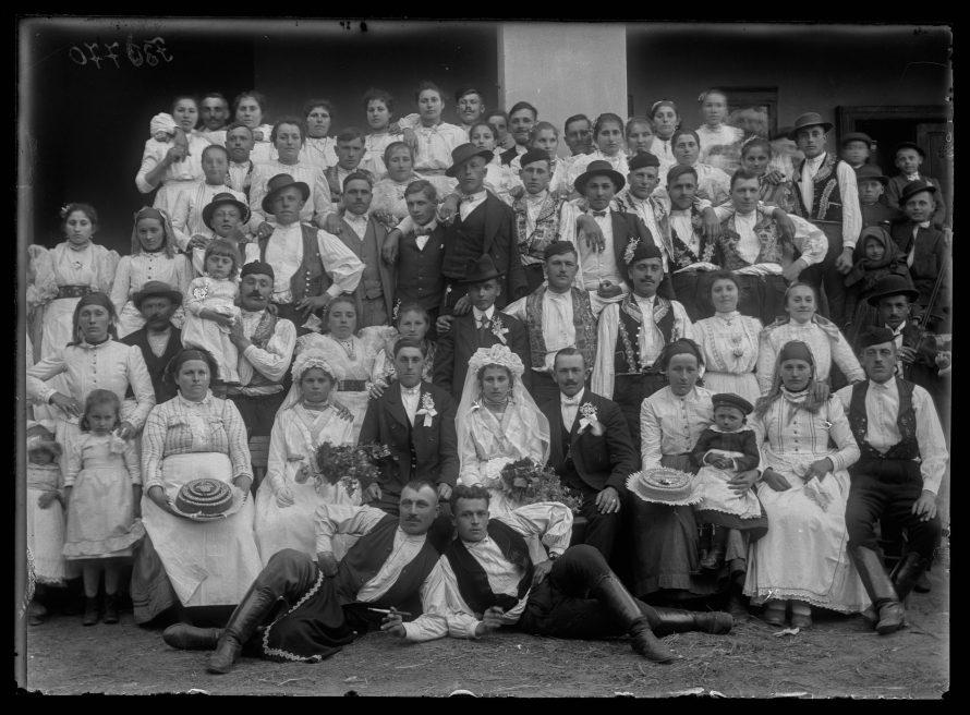 Fotó: Menyasszony és vőlegény a násznéppel, jól mutatja a hagyományos kapuvári viselet és a polgári öltözet egymásmellettiségét Kapuvár, 1910-es évek<br> Karinger Károly felvétele Néprajzi Múzeum, F 30770