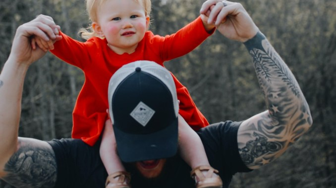 Tattooed father with their child on their shoulder