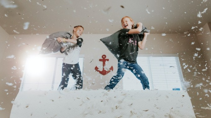 Two children having a pillow fight on their bed - punk family