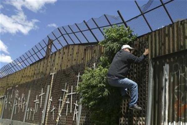 Foto de archivo de una persona intentando trepar el muro fronterizo entre la localidad mexicana de Nogales y Arizona en Estados Unidos, mayo 1 2010. El plan de Estados Unidos para construir un muro en su frontera sur causó protestas en México y dividió a los estadounidenses cuando fue aprobado en una ley en el 2006, pero el tema quedó ensombrecido a raíz de la recesión económica del año pasado. REUTERS/Alonso Castillo
