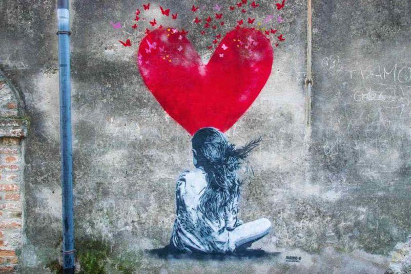 disegno del writer Kenny Random con bambina e grande cuore rosso che si apre in mille farfalle volanti