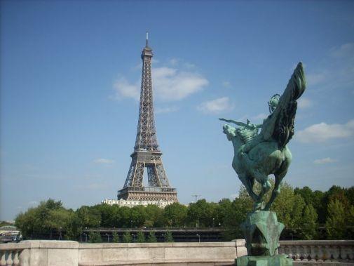 statua di cavaliere con cavallo con lancia che punta direttamente alla tour eiffel sullo sfondo