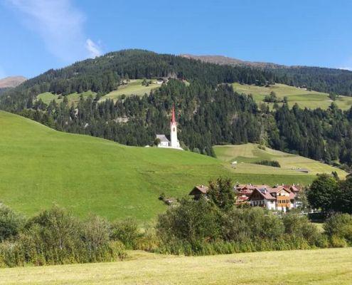 Veduta del panorama con chiesa sullo sfondo nella ciclabile San Candido Lienz