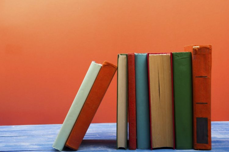 Books bound in red, blue and green fabric standing up against an orange background.