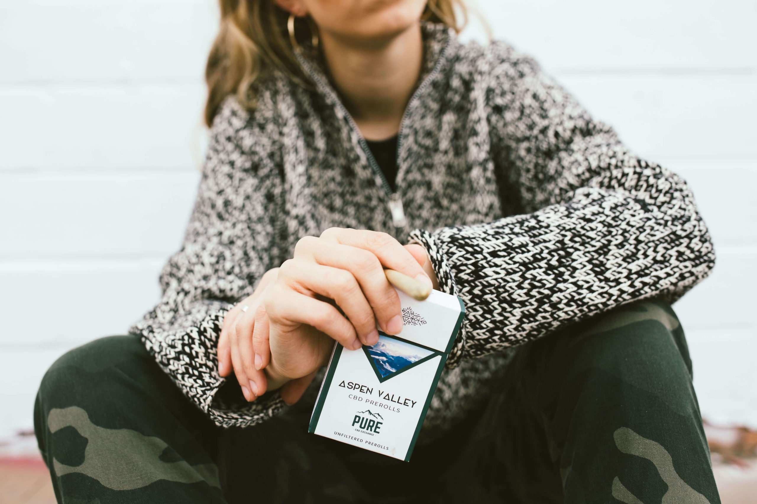 A girl sitting and holding a pack of Aspen Valley Hemp Company CBD Joints