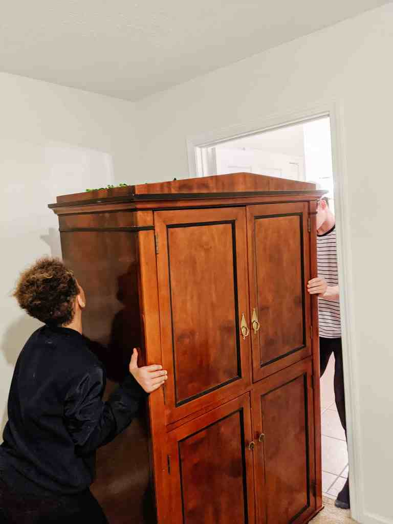 wood armoire being moved