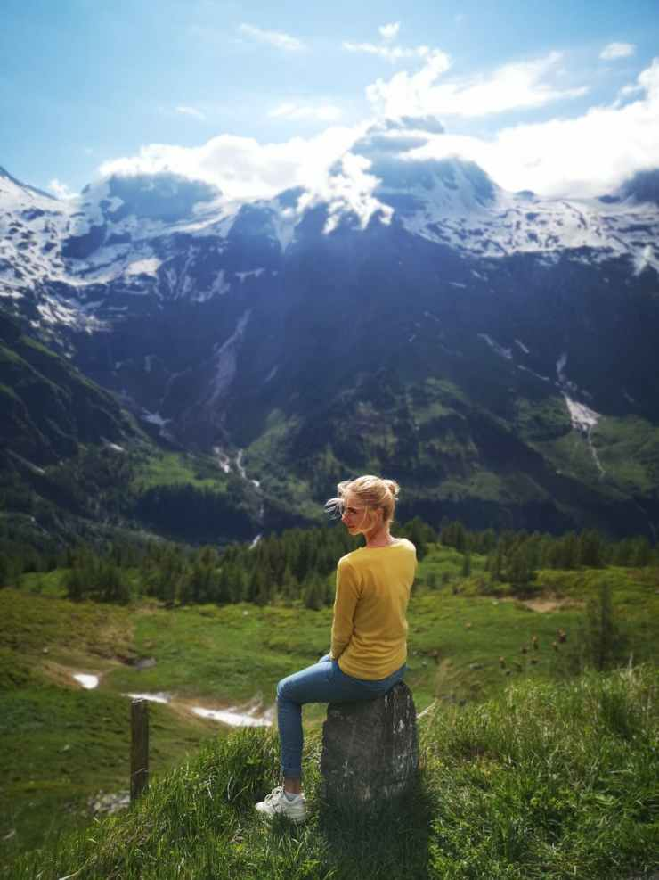 slim woman resting on stone and looking at mountains