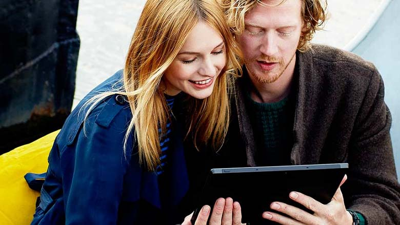 Two people posing using a Windows 8.1 tablet