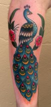 This-old-school-style-tattoo-depicts-a-peacock-sitting-in-a-tree-displaying-its-colorful-feathers1