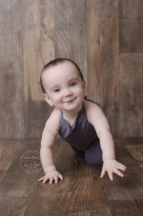 baby-photos-milestone-10-months-smiling-sitting-barnwood-floor-upcycled-purple-knit-sweater-sitter-romper-crawling