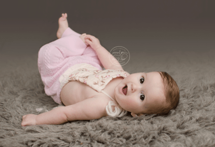 ellie-7-months-sitting-milestone-Ellie-baby-grey-flokati-sitter-pink-vintage-cabled-upcycled-romper-daddymackhats-900x615