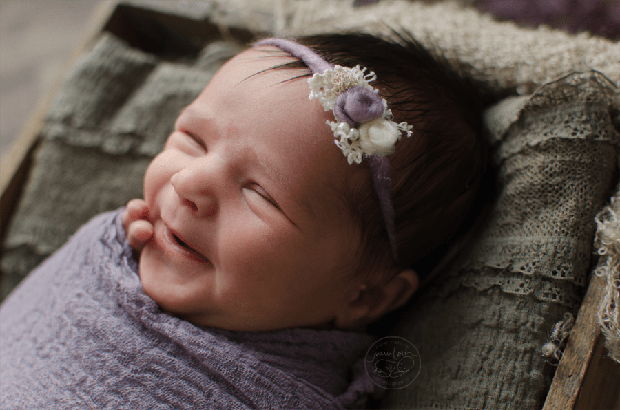 10 days new, baby Aurelie -- antique violet cheesecloth wrap, baby smile, vintage wood crate, lavender floral Dear Felicity tieback | Pure Natural Newborn Photography, Barrhaven / Ottawa