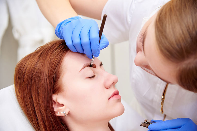 Young woman on eyebrow correction in cosmetology clinic.
