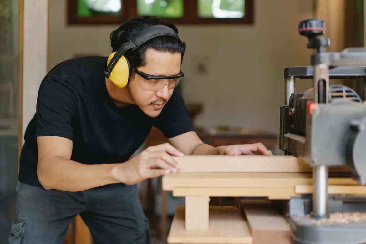 attentive asian joiner leveling timber on planer in workshop
