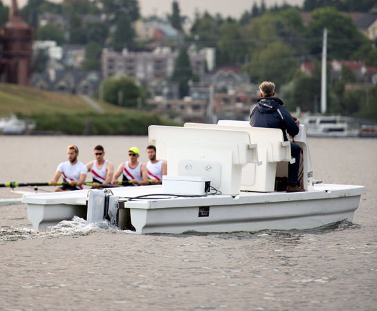 Man driving electric powered coaching launch at rowing practice