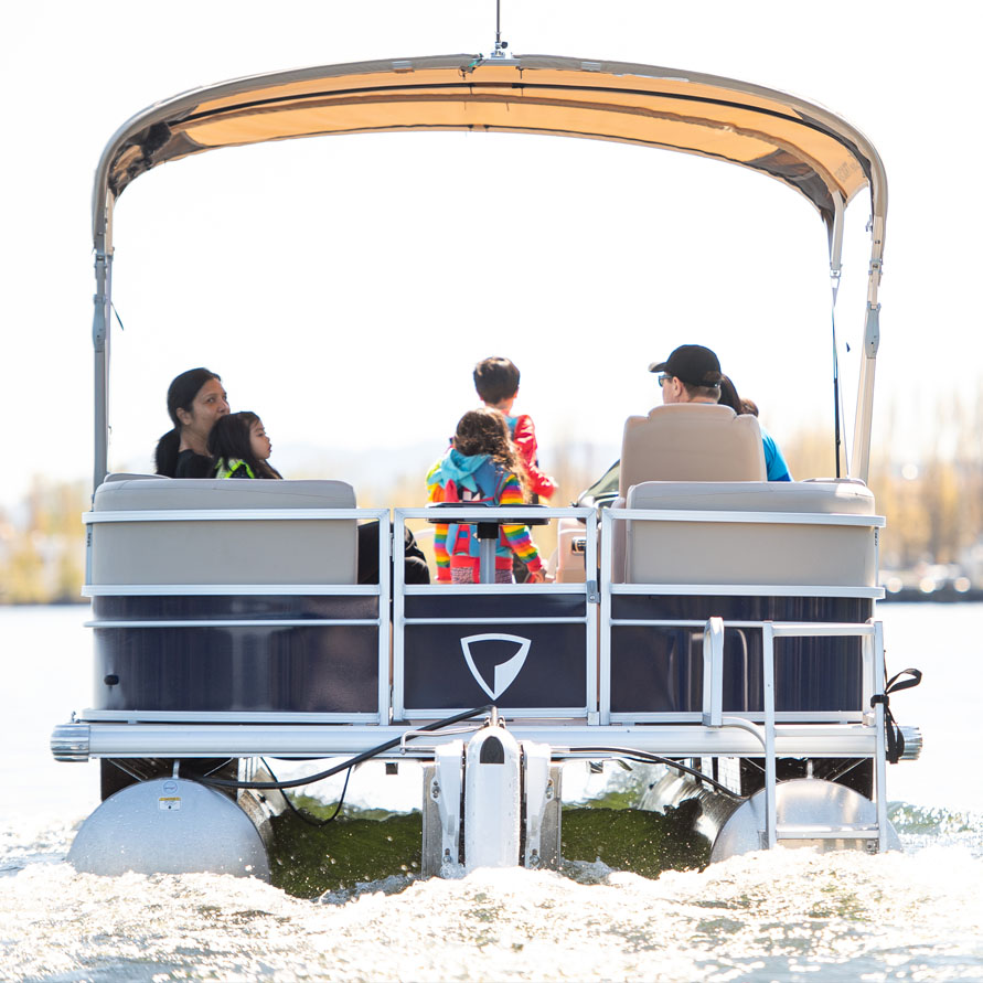 Electric powered pontoon boat from the stern with family