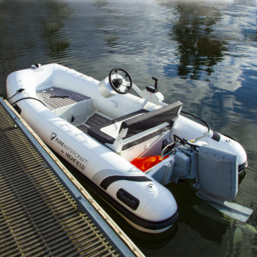 Electric powered rigid inflatable boat tied to dock
