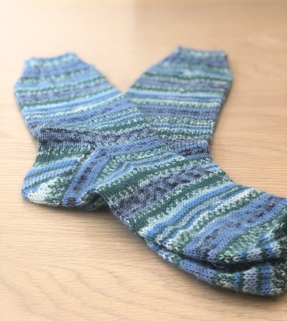 A pair of socks on a wooden table knitted in Arne & Carlos Winter Night Yarn