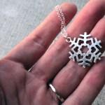 Silver snowflake love necklace in hand, minimalist jewelry design by Liz @PurlsAndPixels