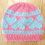 Handmade pink baby hat with blue hearts for twin baby gift set. Hand-knit by Liz @PurlsAndPixels.