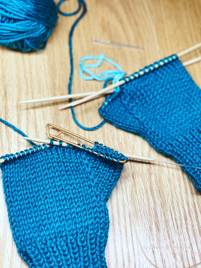 How to separate sections of knitting, such as glove hands and thumbs, with stitch holders - knitting lesson with Liz @PurlsAndPixels.