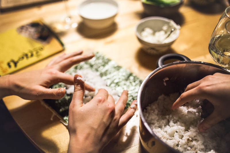 Hands prepping sushi