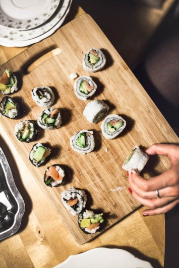 Different pieces of sushi on a wooden cutting board