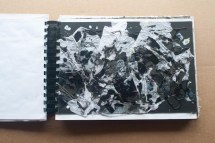 This is a collage of black mountboard card, white plastic bag, tissue, dripped black and white wax and purple staples.