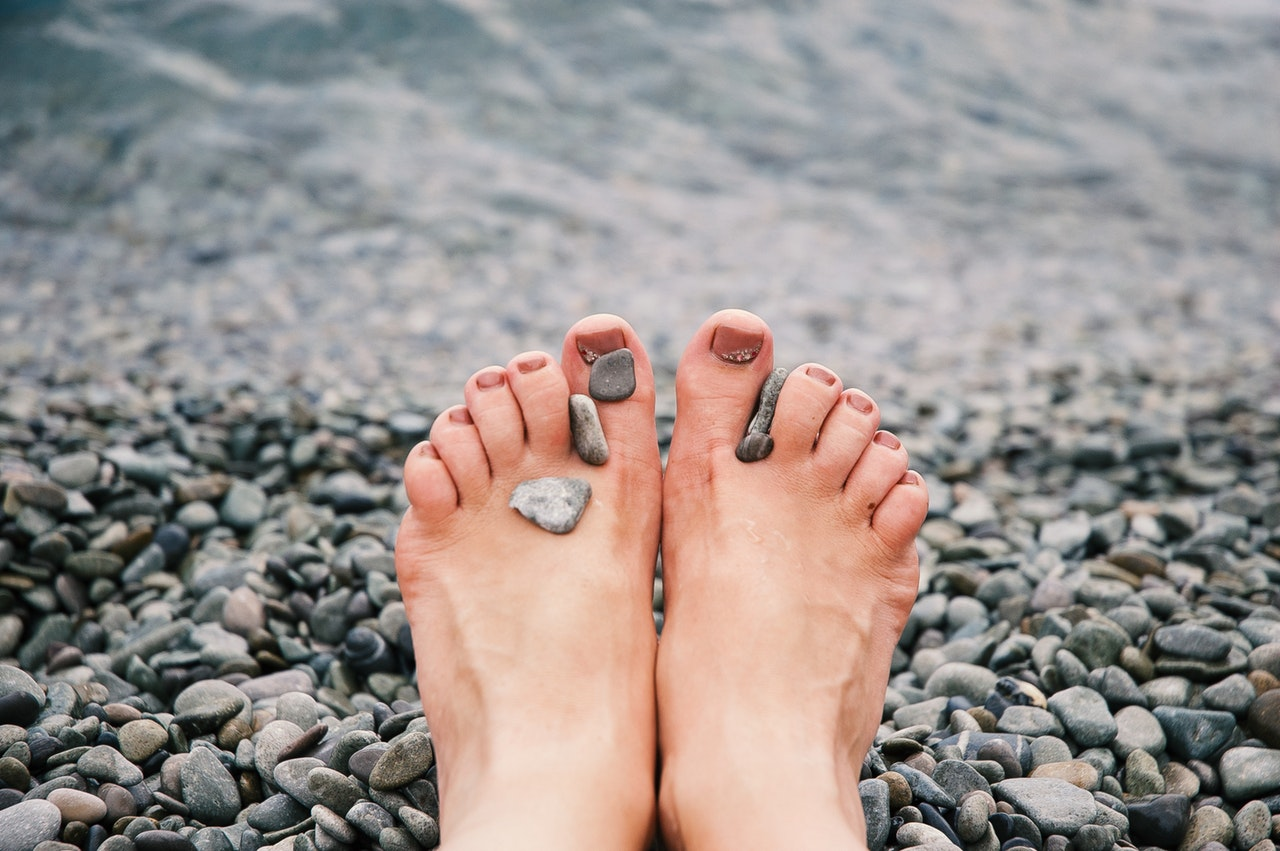 Woman's feet surrounded by stones - reflexology