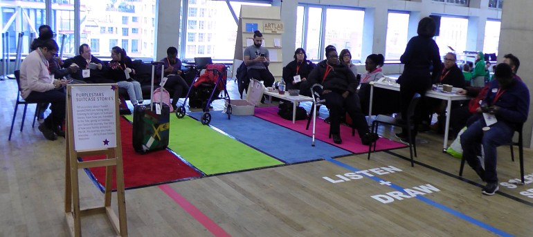 14 purpleSTARS creating an installation group sit on sofas like a airport waiting lounge. The public were invited to join them to record a suitcase story. This was any story about travel, family history and lineage, holiday travel etc.