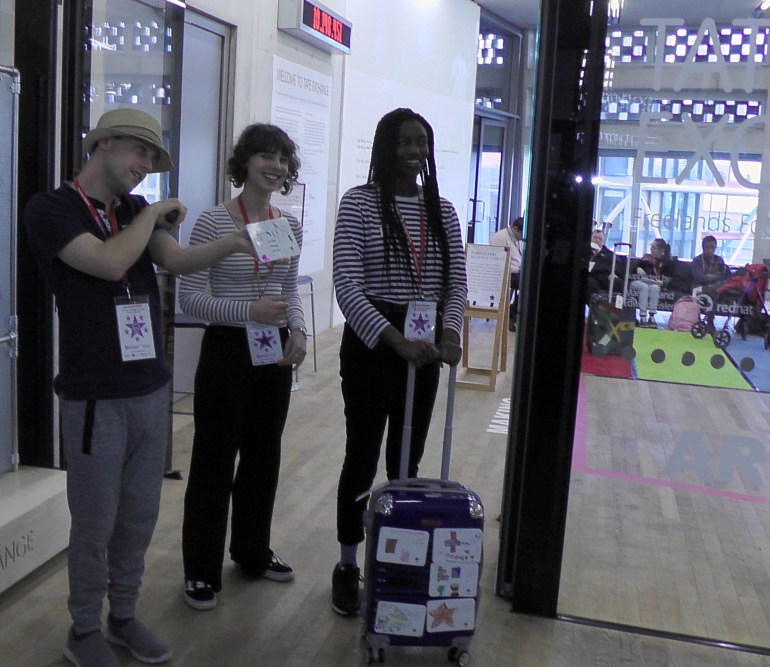 Entrance to Tate Exchange Michael, Becca and Khadija standing with the story suitcase with recordable postcards inviting the public inside.