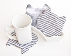 Still life photo of 3 cat shaped cup coasters striped, with a white mug.