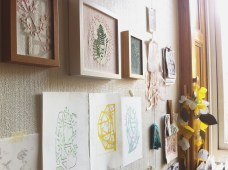 Still live picture of a group of art prints and framed textile artworks on a wall.