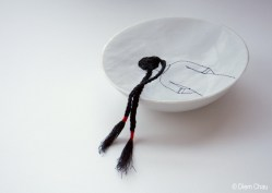 Still life photo of a porcelain bowl with an illustration of a girl seen from her back with long braids, realised with thread.
