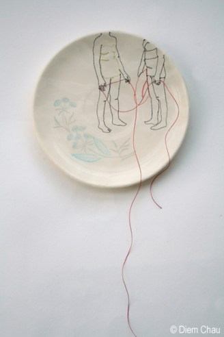 Still life photo of a porcelain plate seen from above with an illustration of two people holding a red thread.