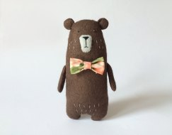 Still life of a Felt Brown Bear With Bow surrounded by a white background.
