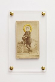 Still life photo of a framed vintage portrait sewed with a golden thread.