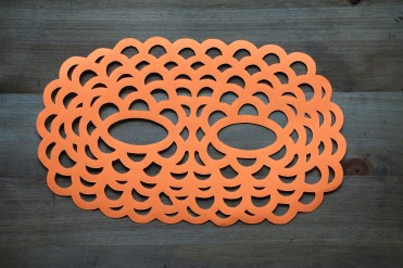 Still life photo of an orange paper mask seen from above.