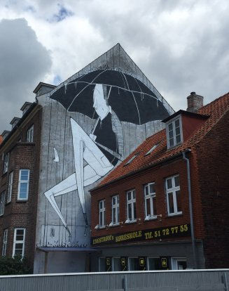 Photo of a wall of a building decorated with an illustration of a man with an umbrella.
