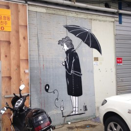Photo of a grey wall decorated with an illustration of a man seen from its back holding an umbrella.