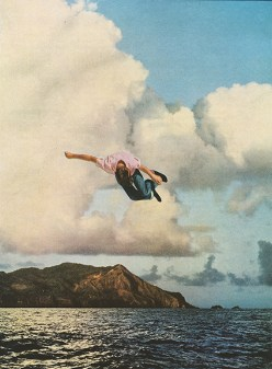 Man jumping into the air over a seascape.