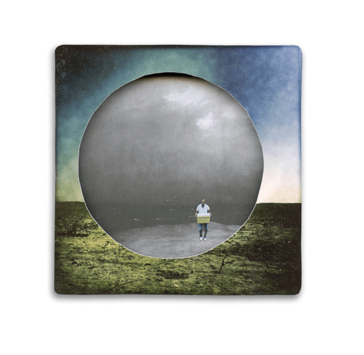 rounded paper cut of a landscape with a man walking inside.