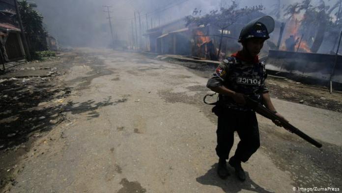 Scena iz Arakana. Mijanmarski policajac na dužnosti. U pozadini je muslimanska kuća u plamenu
