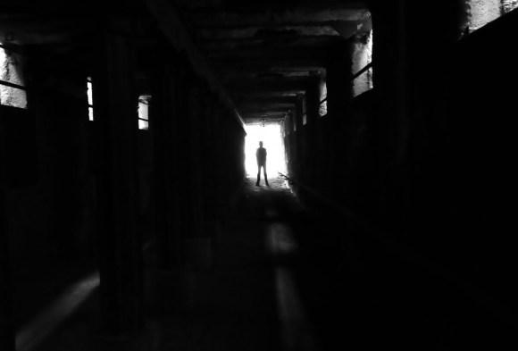 Shadow of man standing in dark tunnel