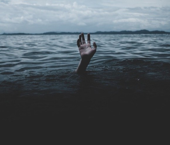 Dark water with hand coming out