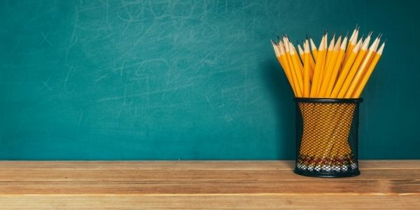 Pencils in cup in front of chalkboard