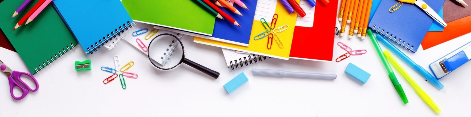 School Supplies scattered on a white desk background
