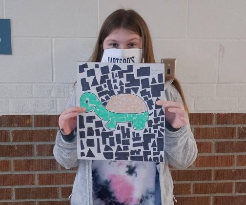 Student posing with artwork of a turtle